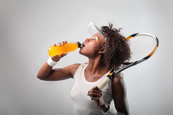 Donna africana con una racchetta da tennis che beve una bevanda sportiva