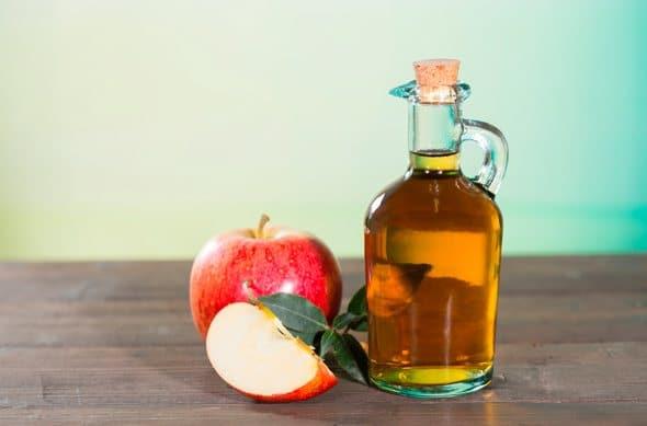 Aceto di sidro di mele, una mela intera e una fetta di mela