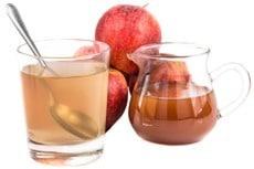 Aceto di sidro di mele in un bicchiere e una brocca