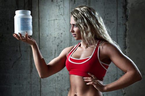 Donna atletica che tiene un contenitore con proteine
