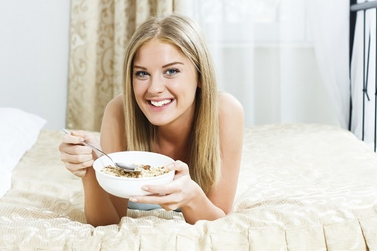Bionda mangiare farina d'avena a letto