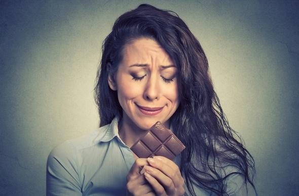 Bruna che piange su una barretta di cioccolato