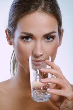 Bruna che beve da un bicchiere d'acqua