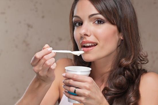 Bruna che mangia yogurt con un cucchiaio