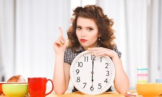 Bruna che tiene un orologio e in attesa di mangiare
