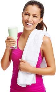 Bruna che tiene un frullato di proteine e sorridente