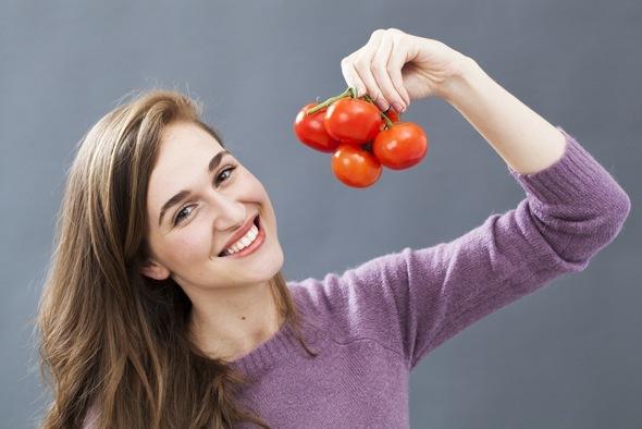 Bruna che tiene un mazzo di pomodori