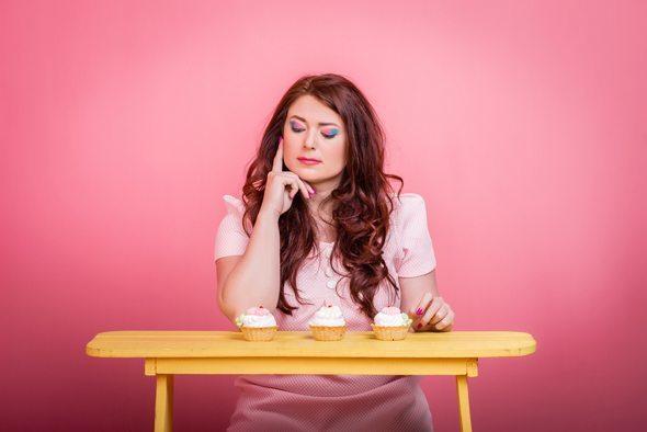 Brunette guardando i muffin zuccherini