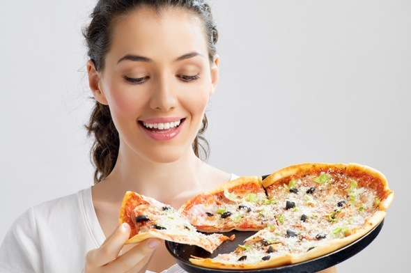 Bruna guardando una pizza e sorridente