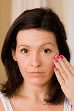 Bruna che tocca la pelle sul suo viso