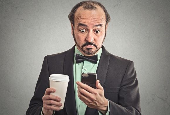 Uomo d'affari che beve caffè guardando il telefono