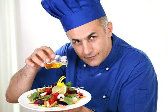Chef versando olio d'oliva su un'insalata, più piccola