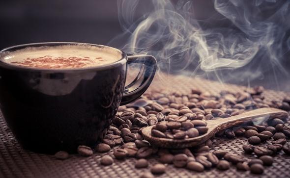 Chicchi di caffè e tazza fumante
