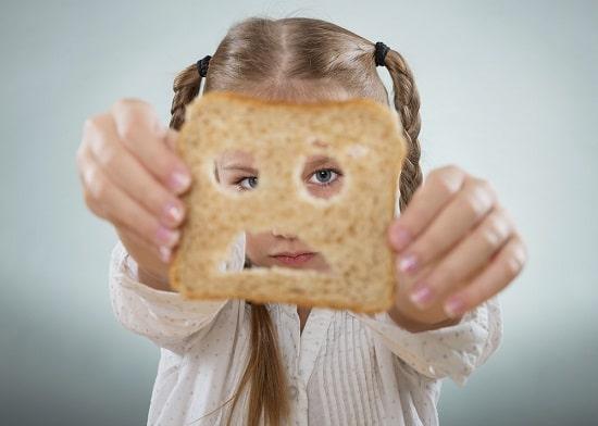 Ragazza che osserva attraverso una fetta di pane