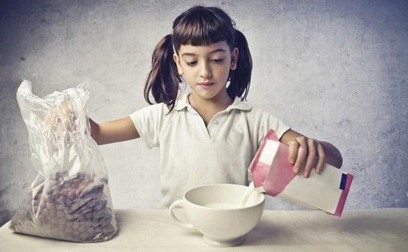 Ragazza che versa il latte nella ciotola di cereali