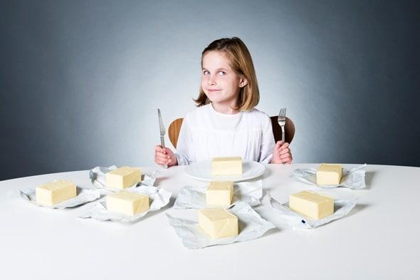 Ragazza seduta a un tavolo con otto blocchi di burro