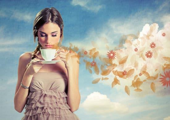Ragazza che sente l'odore della tazza di caffè