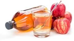 Un bicchiere e una bottiglia di aceto di mele e alcune mele