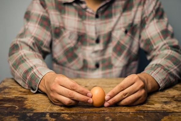 Mani che tengono un uovo sodo