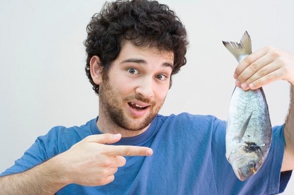 Uomo che tiene un pesce intero