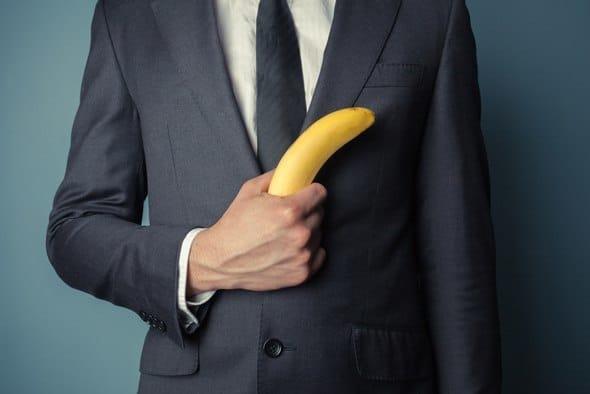 Uomo in vestito che tiene una banana