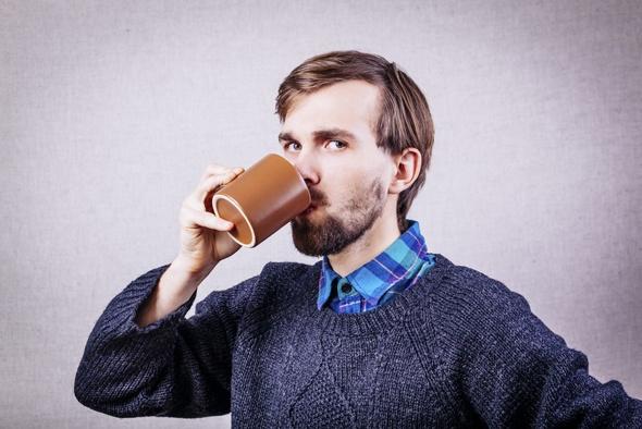 Uomo con la barba che beve caffè