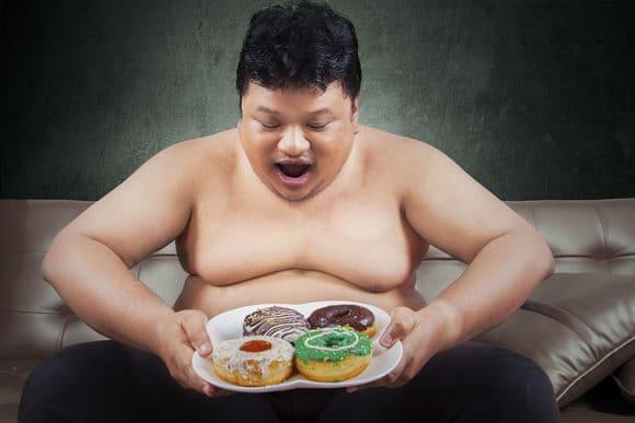 Uomo obeso guardando le ciambelle