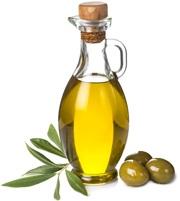 Olio d'oliva in una bottiglia di vetro e tre olive verdi e foglie