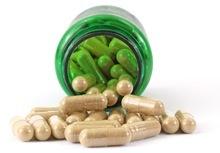 Bottiglia verde aperta piena di capsule