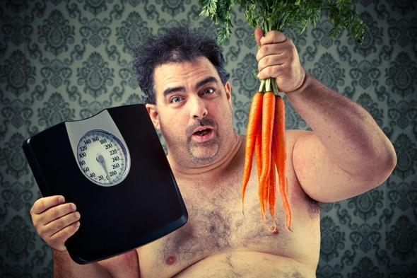 Uomo in sovrappeso con scala e carote