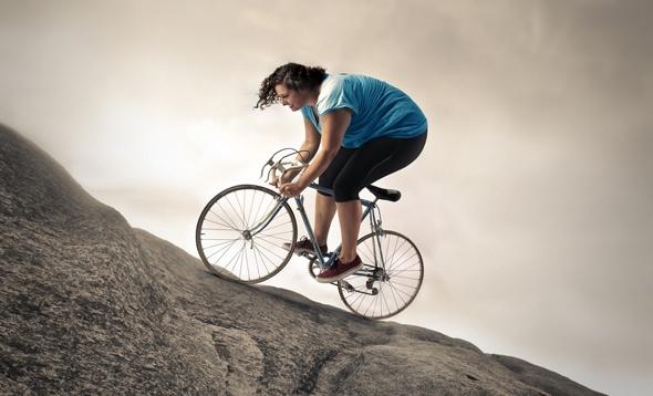 Donna in sovrappeso in bicicletta su un pendio ripido