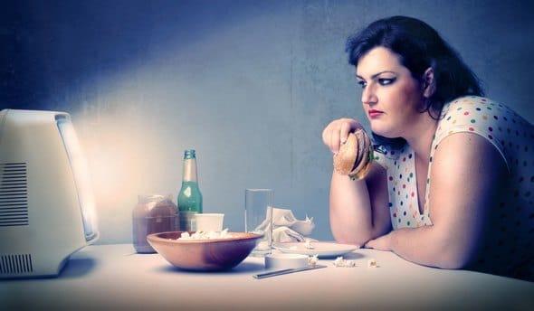 Donna di peso eccessivo che mangia davanti alla TV