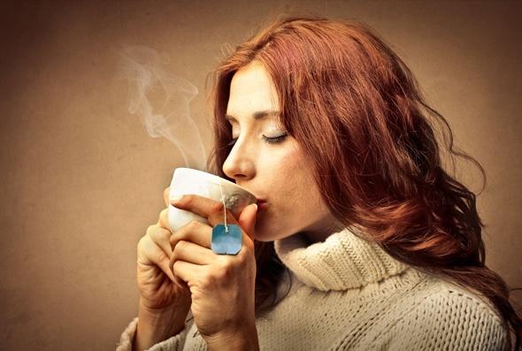 Redhead che beve una tazza di tè
