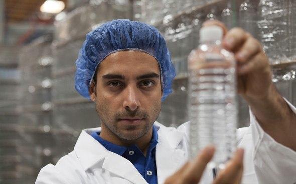 Scienziato che tiene la bottiglia di acqua di plastica