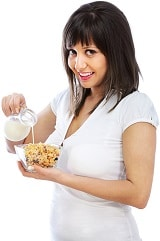 Sorridente bruna versando il latte sui cereali