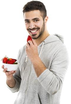 Uomo sorridente che mangia le fragole