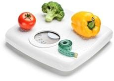 Pomodoro, broccoli, un peperone e un metro a nastro sulla bilancia da bagno
