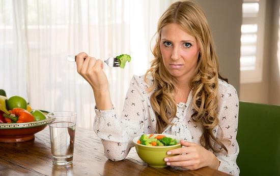 Donna infelice con una ciotola di verdure
