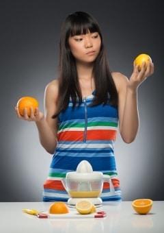 Donna che considera limone o arancia