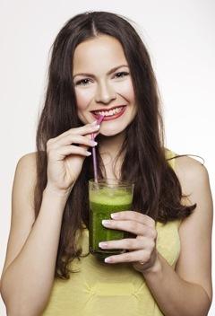 Donna che beve frullato verde con una cannuccia