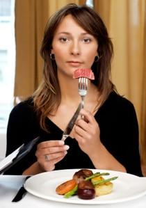 Donna che mangia carne