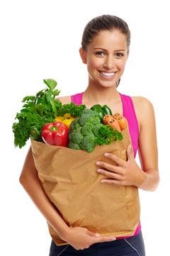 Donna che tiene la borsa della spesa piena di verdure sane