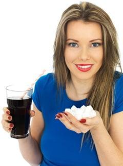 Donna che tiene soda e zucchero