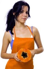 Donna in grembiule arancione che tiene papaia