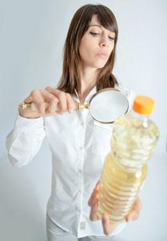 Donna Ispezione Bottiglia Di Olio Con Lente D'ingrandimento