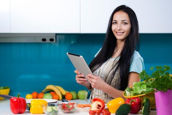 Donna su Tablet in cucina con frutta e verdura