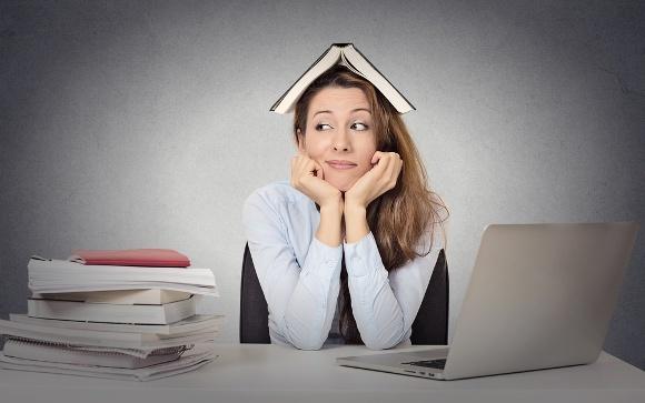 Donna seduta al computer con i libri