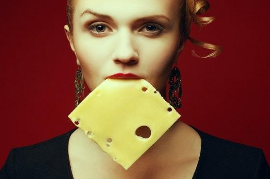 Donna con una fetta di formaggio in bocca