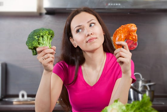 Donna che si chiede se mangiare carne o verdure