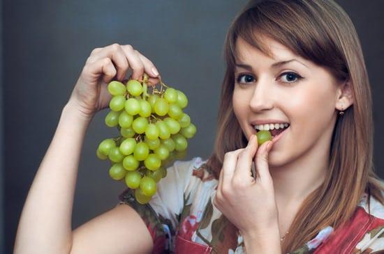 Giovane Donna Che Mangia L'uva Verde